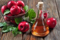 Apple cider vinegar in glass bottle and basket with fresh apples