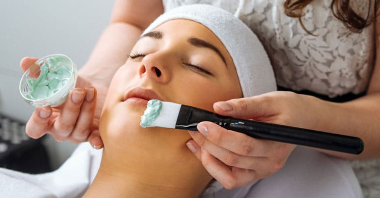Aesthetician applying treatment on face