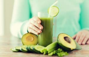 Woman holding glass of avocado smoothie