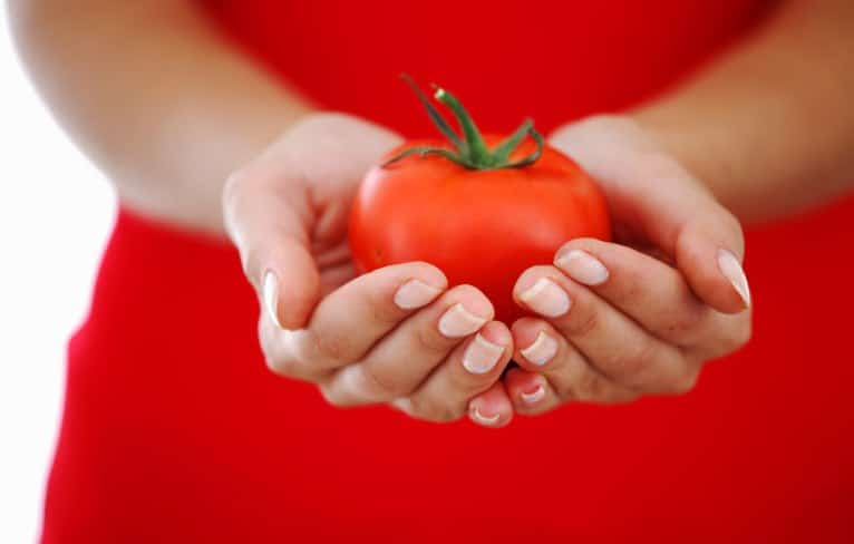 Woman holding a tomato in her hands